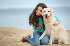 Beautiful girl with her dog near sea Stock Images