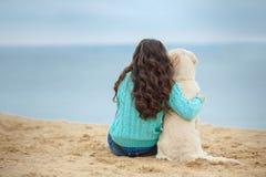 Beautiful girl with her dog near sea Royalty Free Stock Photos