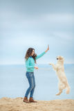 Beautiful girl with her dog near sea Royalty Free Stock Photo