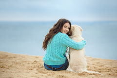 Beautiful girl with her dog near sea Royalty Free Stock Photography