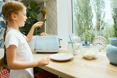 Beautiful girl in her kitchen in the morning preparing breakfast royalty free stock photos