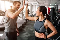 A beautiful girl and her well-built boyfriend are greeting each other with a high-five. They are happy to see each othr. In the gym. Young people are ready to royalty free stock image