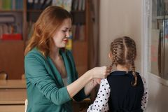 Beautiful girl and her young mother reading a book together or studying at home stock photography