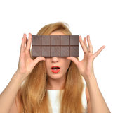Beautiful girl hide her eyes with chocolate bar studio shot Royalty Free Stock Photography