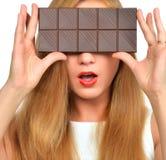 Beautiful girl hide her eyes with chocolate bar studio shot Stock Photo