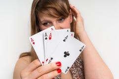 Beautiful girl hides behind poker cards royalty free stock photos