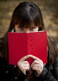 Beautiful girl hiding behind the book Stock Photo