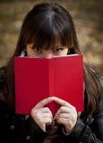 Beautiful girl hiding behind the book stock photo