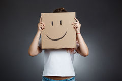 Beautiful girl hiding behind carton with smiley over grey background. Young beautiful girl hiding head behind carton with smiley over grey background. Copy Royalty Free Stock Photos
