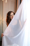 Beautiful girl hiding behind the curtain Royalty Free Stock Images
