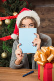 Beautiful girl hiding behind New Year and Christmas postcard Royalty Free Stock Photography
