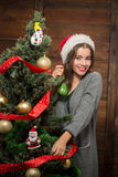 Beautiful girl hiding behind New Year tree Royalty Free Stock Photos