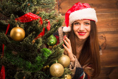 Beautiful girl hiding behind a New Year tree Stock Photos