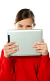 Beautiful girl hiding her face with touch pad Stock Photo