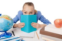 Beautiful girl hiding herself behind a book Stock Images