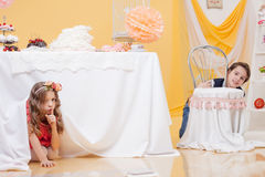 Beautiful girl hiding under table from her brother Stock Images