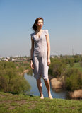 The beautiful girl on high coast. The girl in a dress costs barefooted on high to river bank Stock Photo