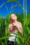 Beautiful girl among high grass of meadow Royalty Free Stock Photo