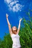 Beautiful girl among high grass of meadow Stock Image