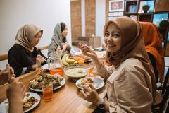 Beautiful girl with hijab smiling and look the camera when eating breaking fast royalty free stock photography