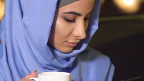 Beautiful girl in hijab using a mobile phone in a cafe. The modern Muslim woman and new technologies.  stock video