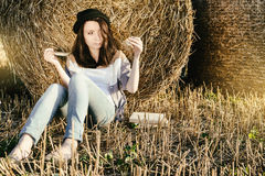 Beautiful girl hipster drink tea against hay bale in fall Stock Image