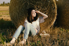 Beautiful girl hipster looks distance against hay bale in fall Stock Image