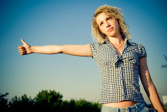 Beautiful girl hitchhiking on the road Stock Photo