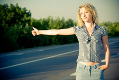 Beautiful girl hitchhiking on the road Stock Photography