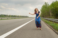 Beautiful girl hitchhiking on the road Stock Images