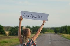 Beautiful girl hitchhiking on the road traveling. royalty free stock photography