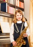 Beautiful girl holding alto saxophone indoors Stock Images