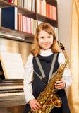 Beautiful girl holding alto saxophone indoors Stock Images