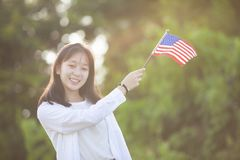 Beautiful girl holding american flag outdoors on summer day. Ind royalty free stock image