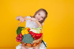 Beautiful girl holding a basket of ripe vegetables healthy food stock image