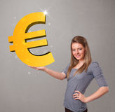 Beautiful girl holding a big 3d gold euro sign Royalty Free Stock Photos