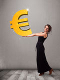 Beautiful girl holding a big 3d gold euro sign Royalty Free Stock Images