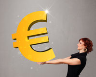 Beautiful girl holding a big 3d gold euro sign Royalty Free Stock Photo