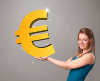 Beautiful girl holding a big 3d gold euro sign Stock Photography