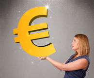 Beautiful girl holding a big 3d gold euro sign Stock Photos