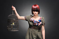 Beautiful girl holding a birdcage Stock Photo