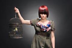 Beautiful girl holding a birdcage Stock Photo