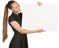 Beautiful girl holding blank white placard and Royalty Free Stock Photo
