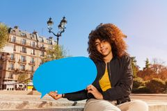 Beautiful girl holding blue blanked speech bubble. Beautiful African teenage girl holding blue blanked speech bubble, sitting on the staircase outdoors at sunny Stock Images