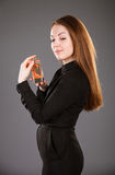 Beautiful girl holding a bottle of perfume. Grey background Royalty Free Stock Images
