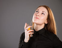 Beautiful girl holding a bottle of perfume. Grey background Royalty Free Stock Photography