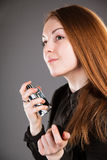 Beautiful girl holding a bottle of perfume. Grey background Royalty Free Stock Photos