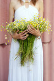 Beautiful girl holding bouquet of camomille flowers in summer Stock Photography
