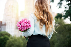 Beautiful girl holding bouquet of pink roses flowers on dating in the city. Stock Images