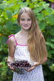 Beautiful girl holding a bowl of cherries in the garden Royalty Free Stock Photos